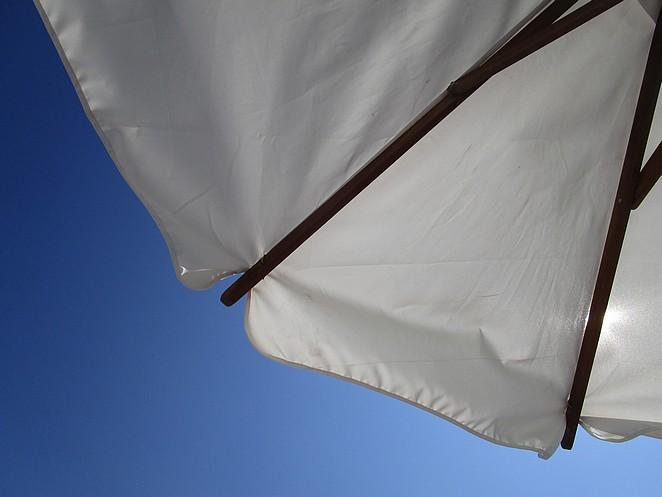 Blauwe lucht witte parasol
