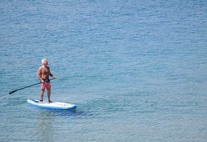 Suppende man aan het strand van s'Agaro