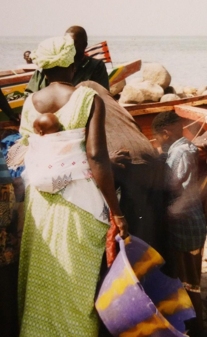 Senegaleze vrouw met baby bij vissersboot