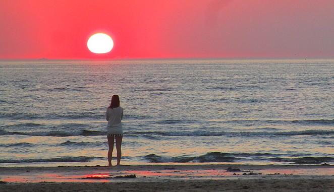 vrouw-zonsondergang-kijken